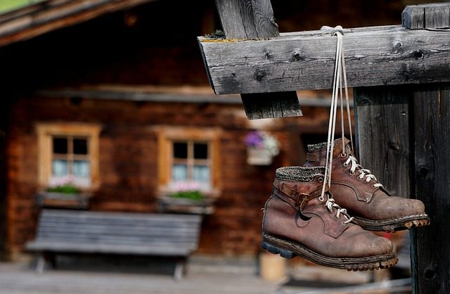 mountain boots hanging on a log